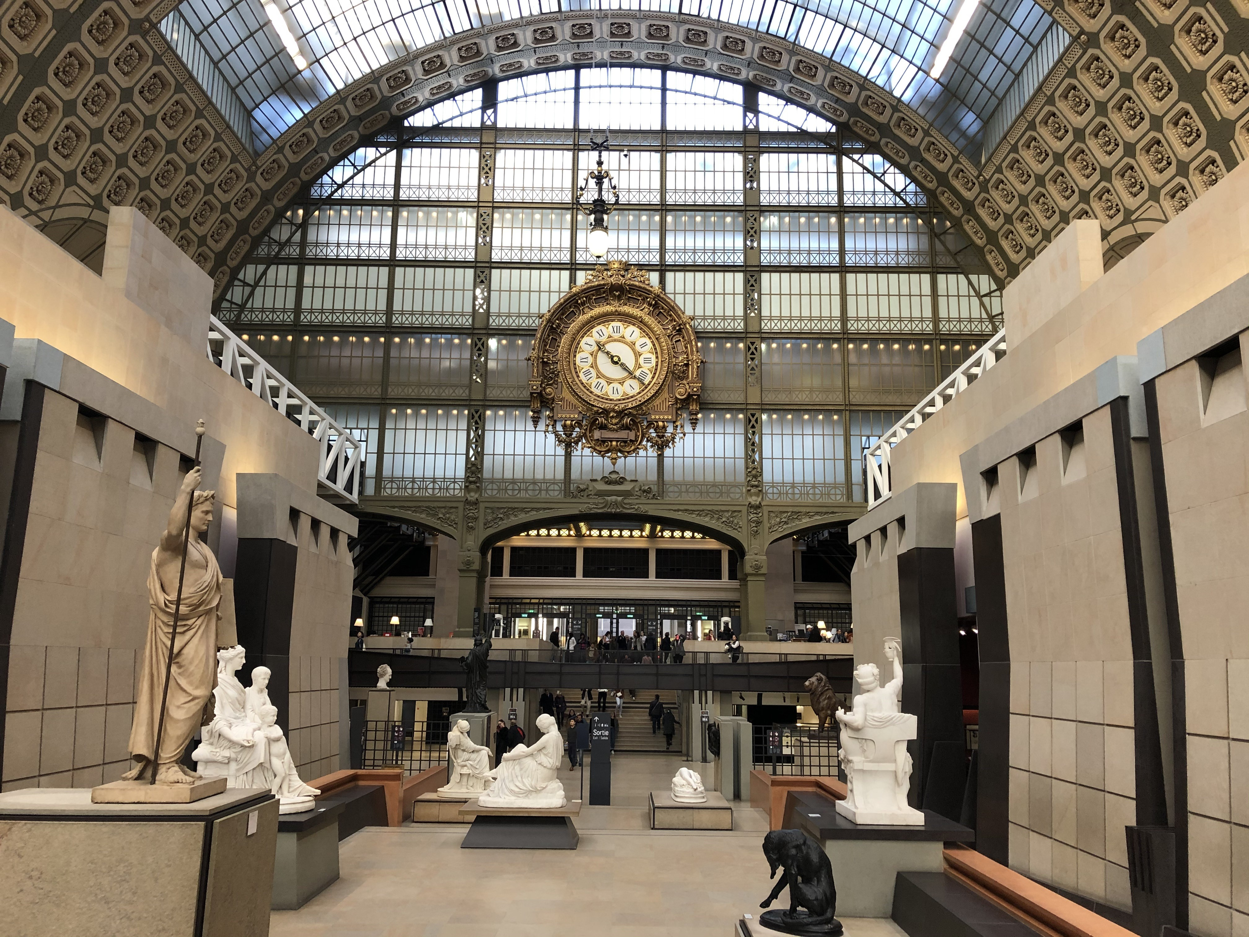 A large space with a glass wall and a clock on the wall with sculptures in the foreground.