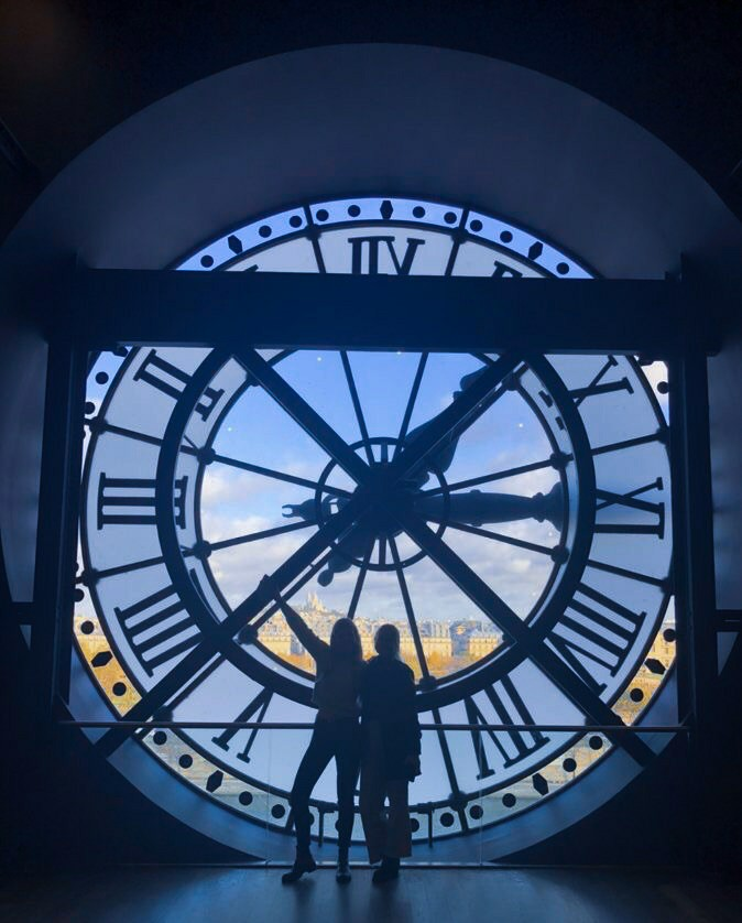 Two people are posing in front of a giant, transparent clock.