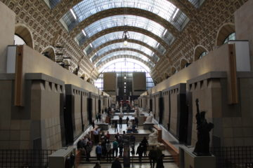 A big space with a glass ceiling and sculptures in the middle passageway.