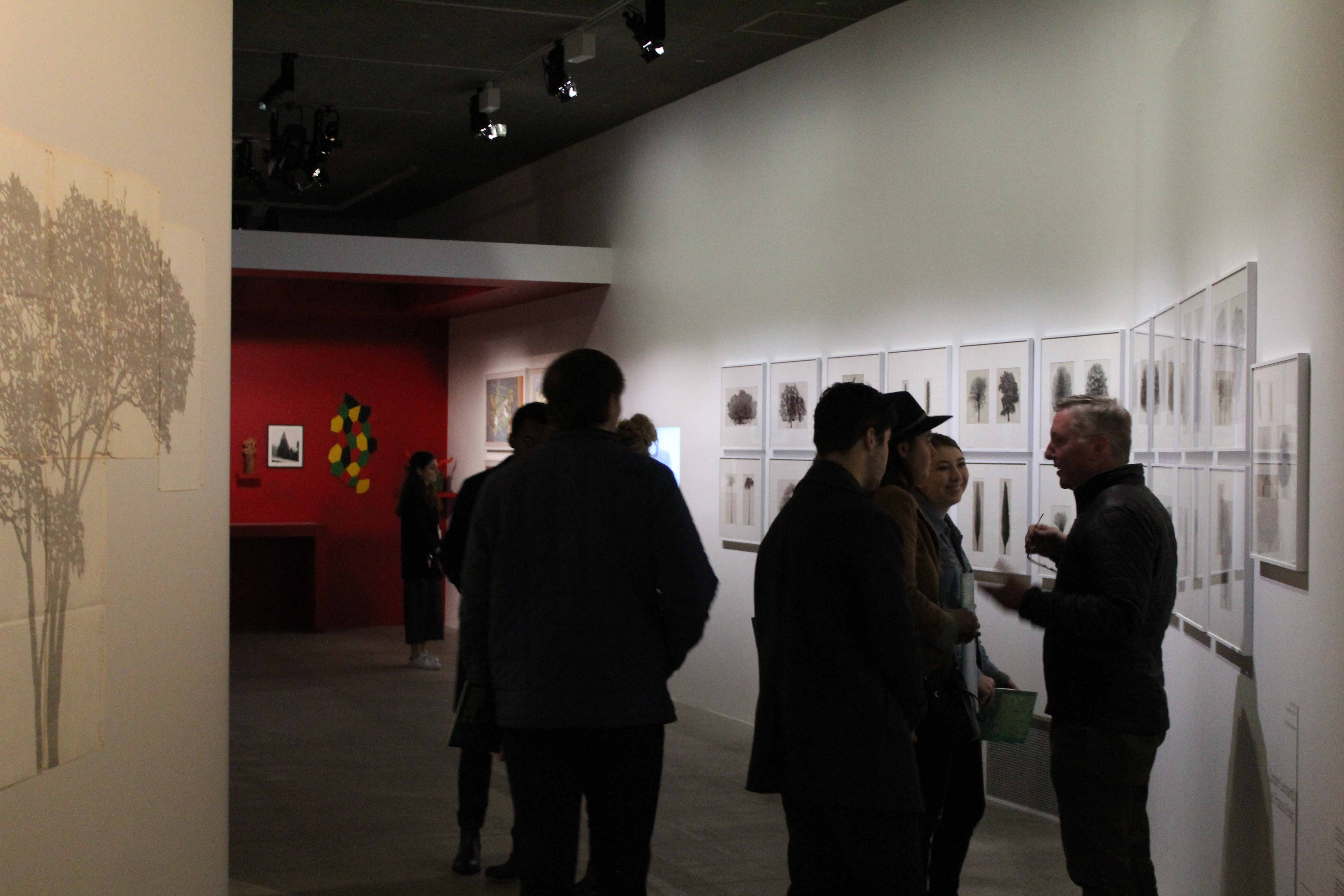 People standing, walking, and talking in a dim lit space with art on the walls.
