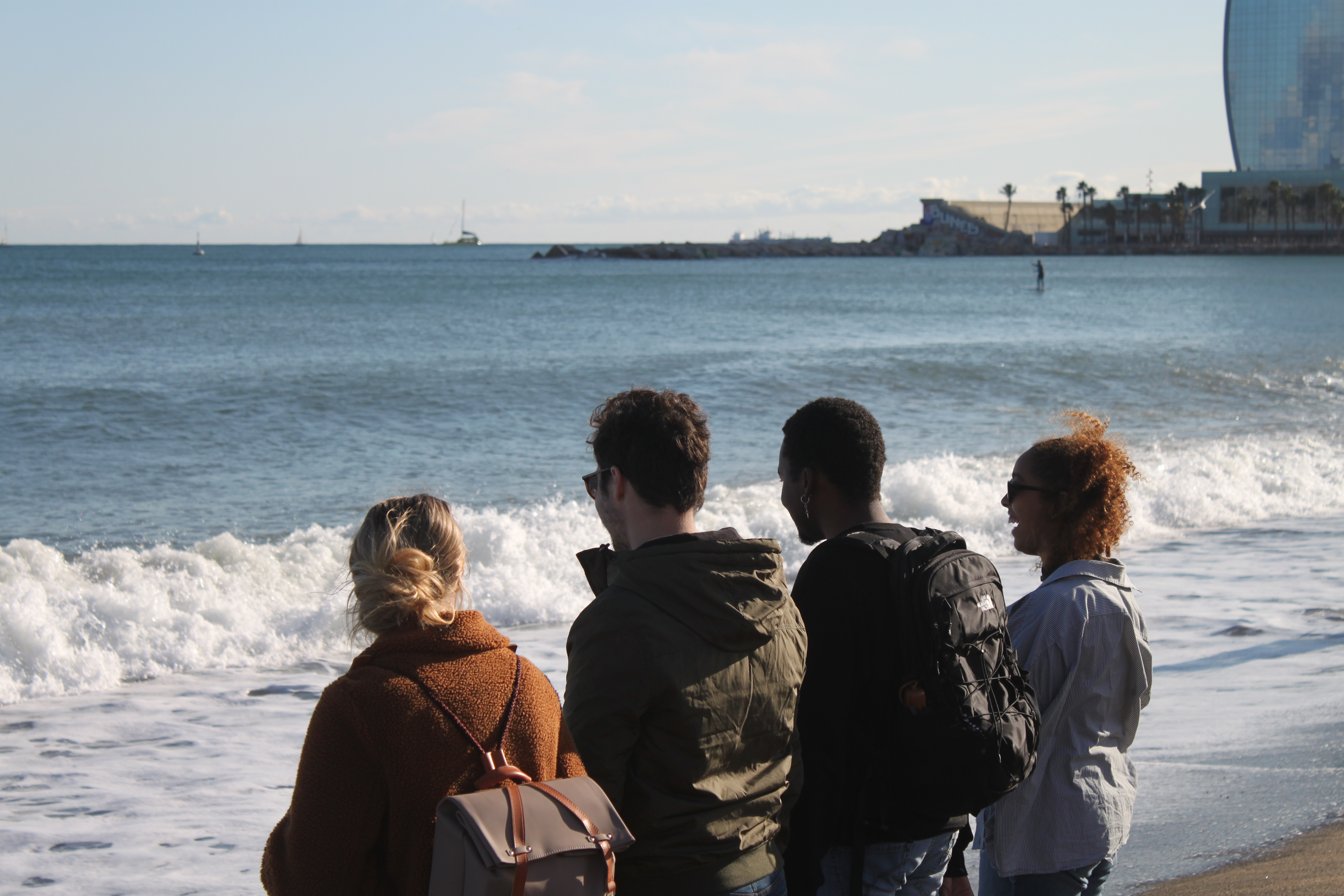 Four people standing near the water on a beach with a person and a building in the background.