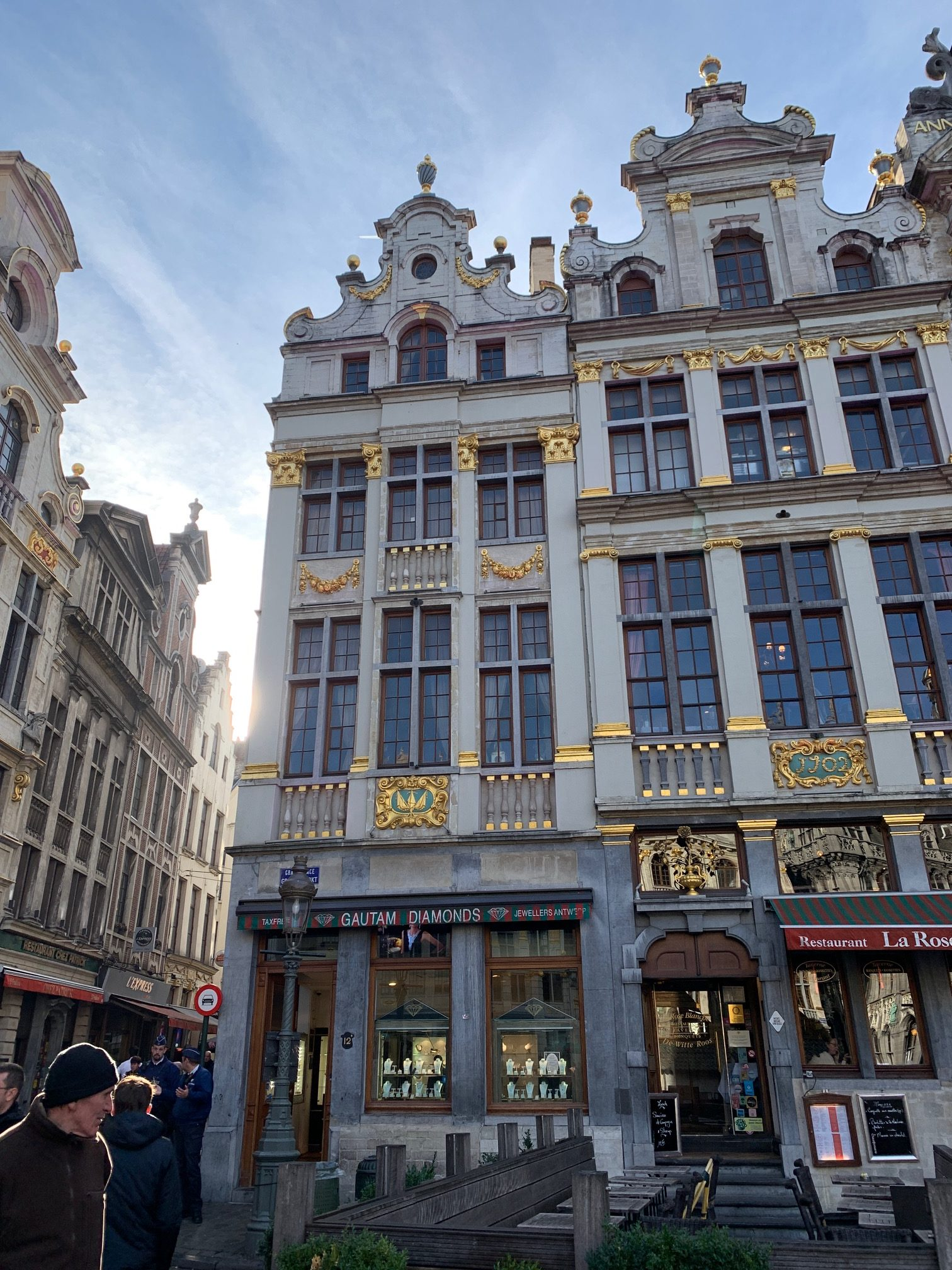 There are buildings with intricate detailing and people in the picture.